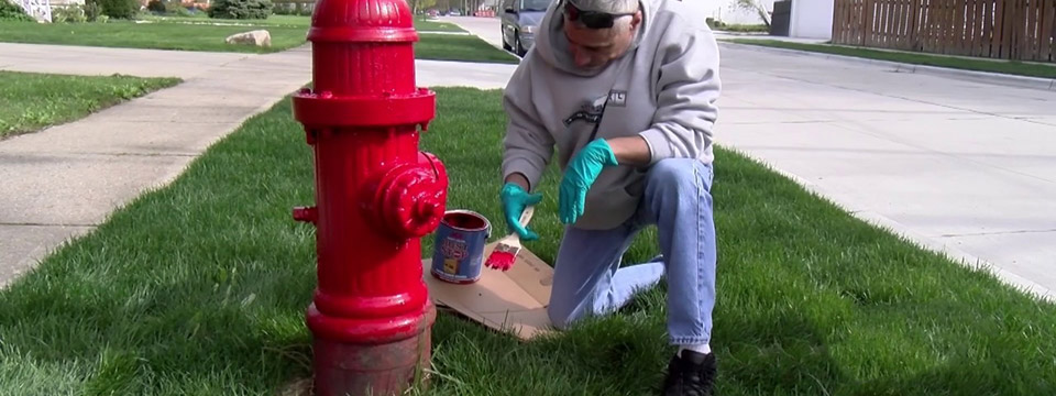 A man kneels on a piece of cardboard while painting a fire hydrant red.