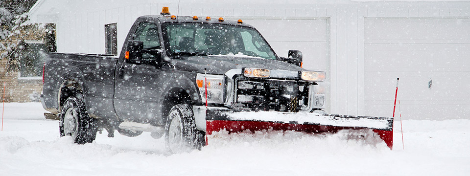 A snow plow operator plows heavy white snow during winter.