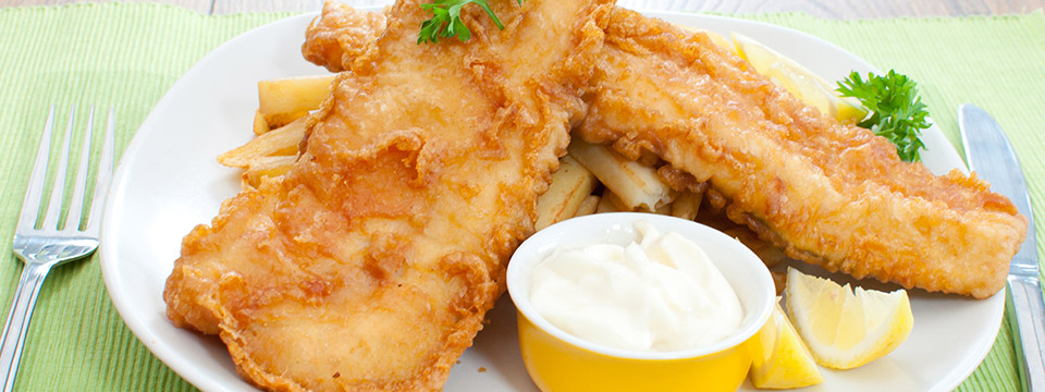 A delicious fish fry platter with french fries, lemon and tartar sauce.