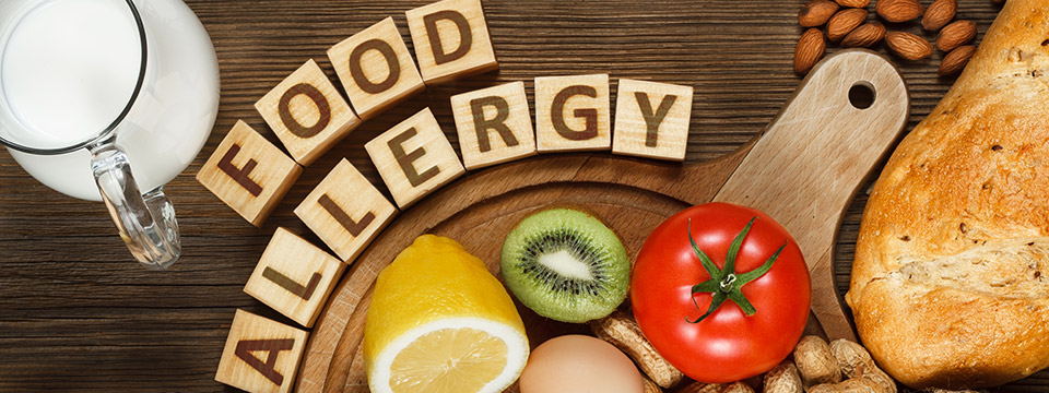 The words Food Allergy are spelled out in wooden blocks which sit on a table above half of a lemon, a kiwi, a tomato, strawberries, eggs, pistachio nuts, peanuts, bread, fish, and other foods.