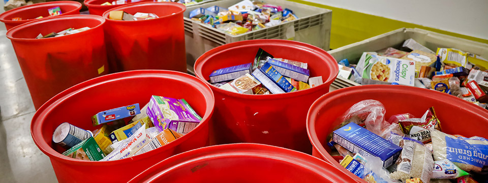 Many large plastic bins filled with donated non-perishables.