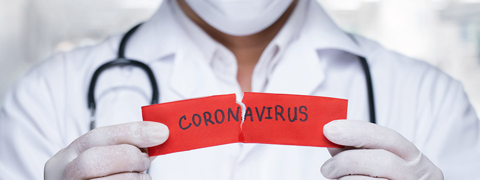 A doctor in gloves and a surgical mask holds up a torn piece of paper with the word coronavirus on it.
