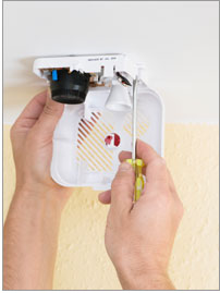 Photo of two hands installing a smoke detector with a screw driver.