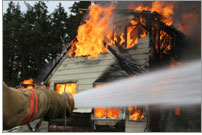 Photo of a fireman holding a hose with water gushing from it. In the background is a house on fire.